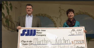 Timothy McLaughlin, SJWC's Community Relations Manager, presents a check to Edita Cruz, Martha's Kitchen Executive Director, to cover all meals served in January.